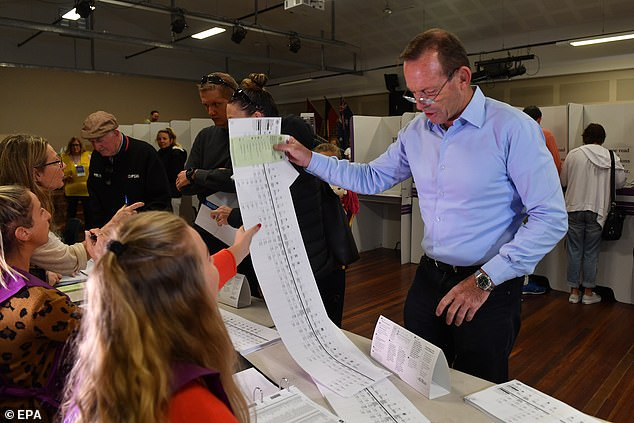 Tony Abbott receives his ballot papers before voting at Forestville Public School during Election Day in Sydney