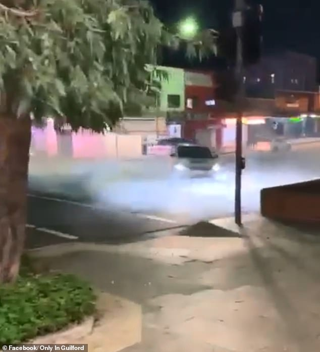 A reckless driver has been filmed doing burnouts in the middle of a busy intersection