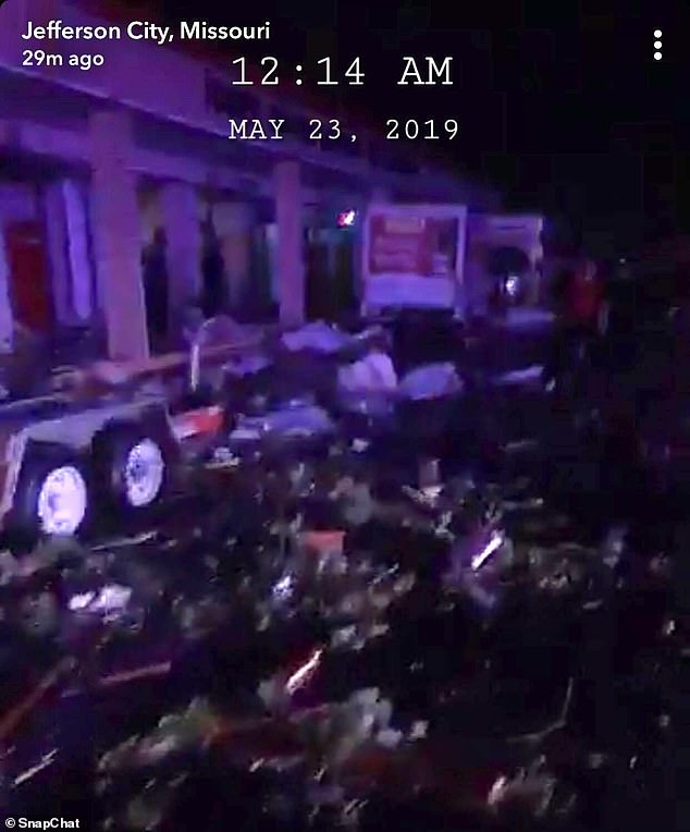 This photos shows debris surrounding a tractor-trailer outside of a building