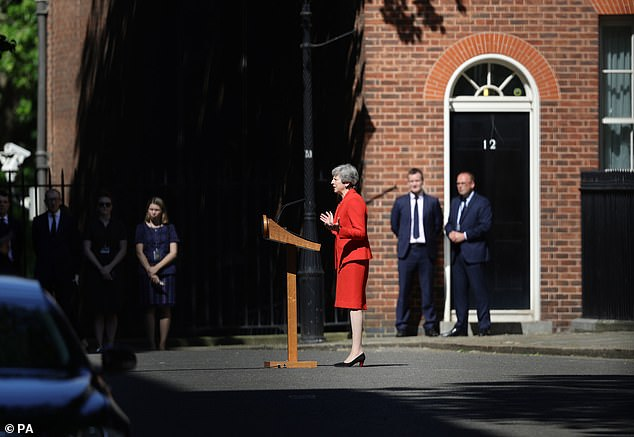 Philip May could be seen watching from the shadows (far left) as his wife delivered her parting message from Downing St