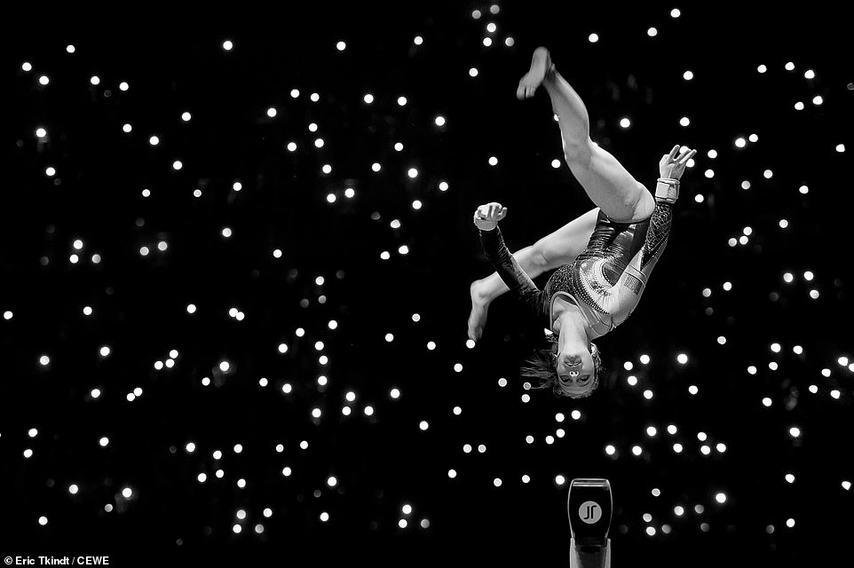 A female gymnast performs an impressive stunt in Antwerp, Belgium. Eric Tkindt, who captured the athlete in action, explains that the lights in the background are from mobile phones.This shot was deemed a monthly winner for April