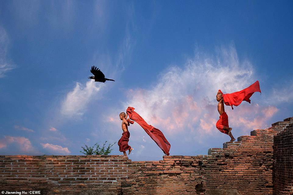 Two young monks run across a crumbling brick wall in the China, in this shot by Jianming Hu