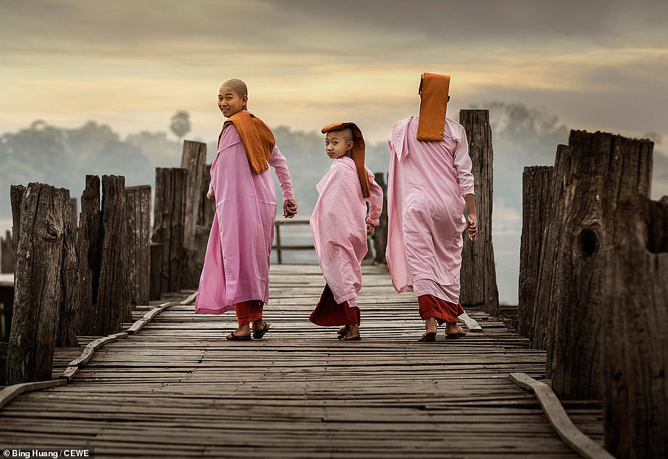 Two girls look back towards the camera as they walk along a wooden pier in Myanmar. The candid shot was captured by Bing Huang