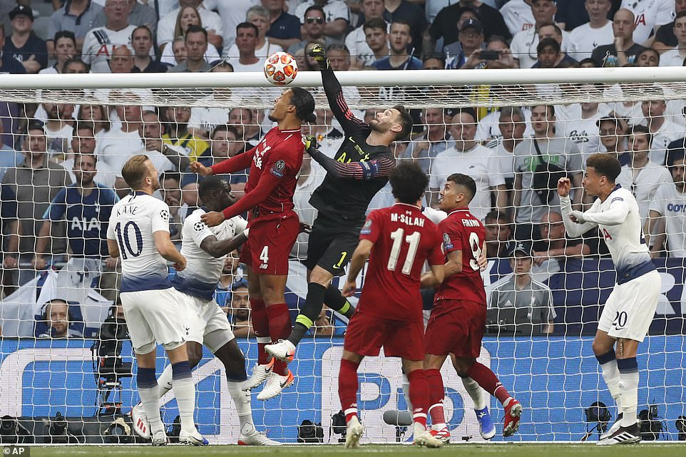 Tottenham goalkeeper Hugo Lloris rises above Liverpool defender Virgil van Dijk to punch the ball clear after a corner