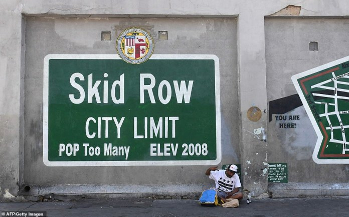 A man makes gestures sitting next to a Skid Row painting on a sidewalk in downtown Los Angeles