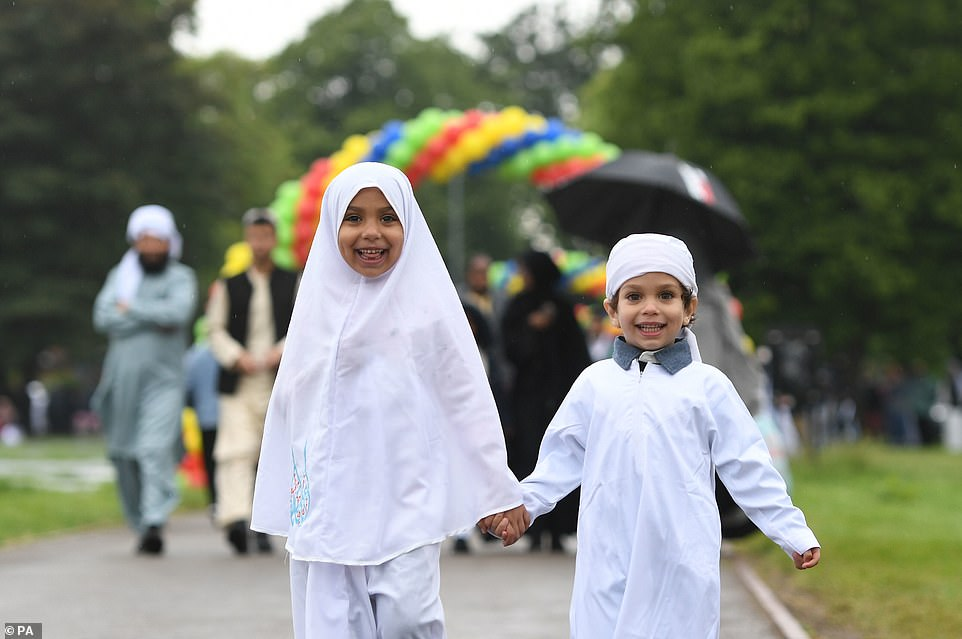 Muhammad, 4, and Sanaa, 6, (left) arrive for the Eid celebrations in Small Heath Park, Birmingham. Police in Greater Manchester are appealing for respect from visitors to the city during the Muslim religious holiday