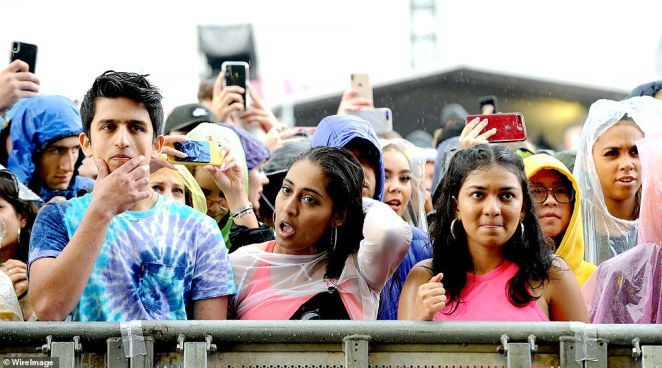 Festival-goers are left wet as they brave the rain in Manchester. Earlier today the Met Office said showers are also due to fall on London on Monday