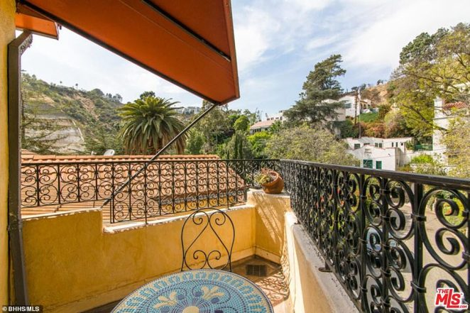 Room with a view: This little balcony leading from one of the bedrooms has a decorative fence and looks out over trees and nearby hillsides and offers a glimpse of other secluded properties in the area