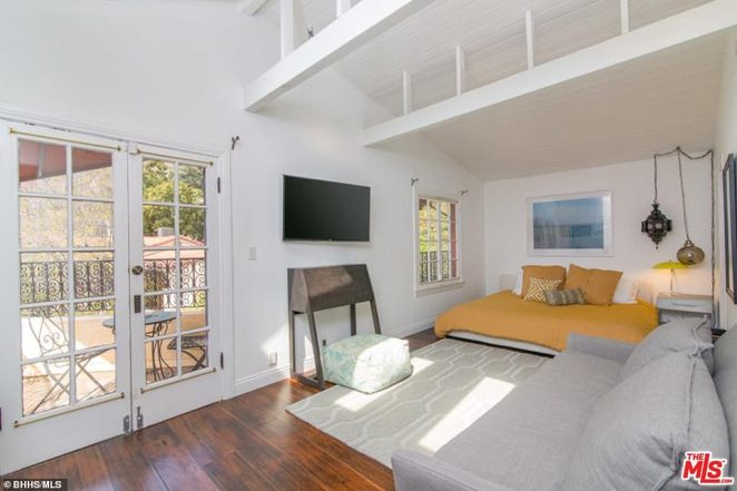 Another bedroom: These sleeping quarters include a sofa and a set of double doors leading on to a balcony. Here, the outdoor area has been furnished with seats and a small table and there is a large TV on the bedroom wall