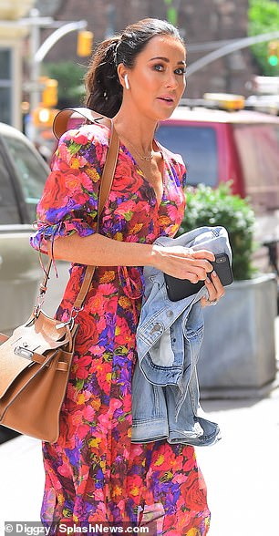 Chic: The mom-of-three wore a multicolored mid-length dress that featured a low-cut neckline and a cinched waist. She teamed the dress with a tan-colored handbag and nude heels