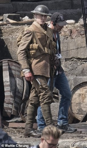 Make way: An actor dressed in period military attire was seen walking across the rubble strewn set