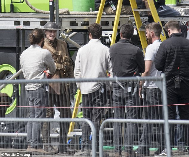 Plenty to talk about: Members of the production team gathered round the actor as they passed the time between takes