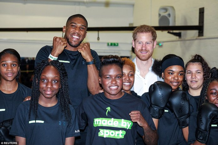 Holding their fists up for a photo, Antony Joshua (back left), Prince Harry and Nicola Adams (centre) smiles for the cameras alongside youngsters at the training school