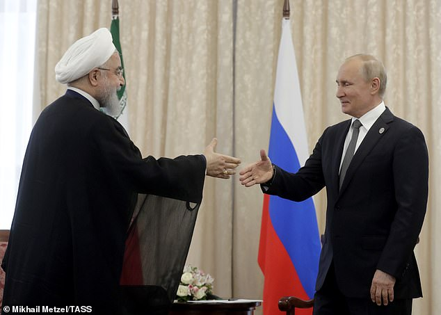 Iranian President Hassan Rouhani (left) and Putin shake hands as they meet on the sidelines of Friday's conference