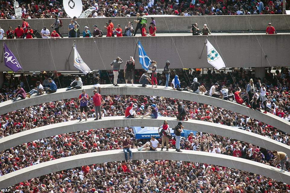 Fans climb the arches at Nathan Phillips Square ahead of Monday's victory parade in Toronto