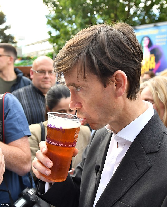 Mr Stewart is pictured with a pint on London's Southbank this afternoon. Mr Stewart again flip-flopped today over whether he would serve in a Mr Johnson Cabinet, telling Good Morning Britain he '100 per cent' would not