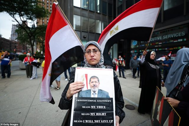 A woman holds a picture of Mohamed Morsi during protests against Egypt's military government in New York on Monday