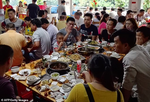 People eat dog meat at a restaurant in Yulin on June 21, 2017. Each year, thousands of dogs are cruelly killed, skinned and cooked with blow-torches during the festival on summer solstice