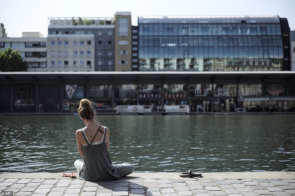 A woman sits under the sun along the Canal de l'Ourcq in Paris on Friday. The country is set for record-breaking searing heat