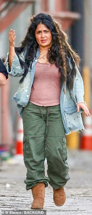 Homeless chic: Hayek donned a maroon tank top under a long-sleeved blue denim shirt, green pants and thick brown boots, with her hair looking knotted and ratty as ever