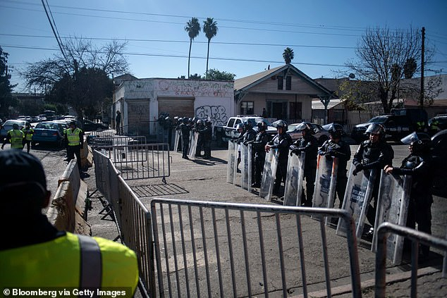 Mexican riot police officers guard the entrance to a makeshift camp for asylum seekers near the U.S. and Mexican border crossing in Tijuana, Mexico in November