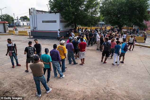 Asylum-seekers wait in line to get a meal close to the International Bridge near a section where a father and daughter drowned attempting to cross into the United States on June 26, 2019