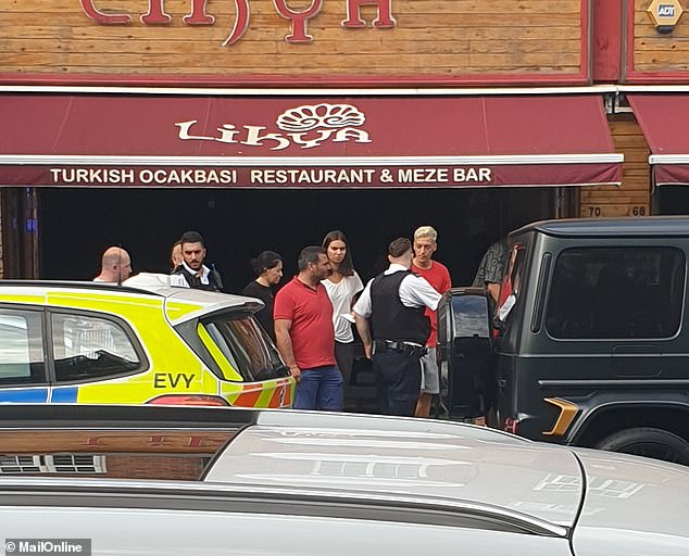 Mesut Ozil (dyed blonde hair) was pictured talking to officers outsideTurkish restaurant Likya on Golders Green Road in north London after the attack last summer