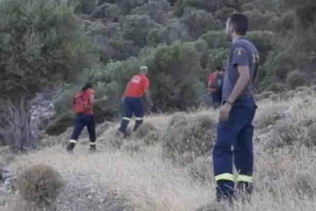 Rescuers head through the shrubbery on the rocky landscape of Ikaria as they looked for Dr Christopher