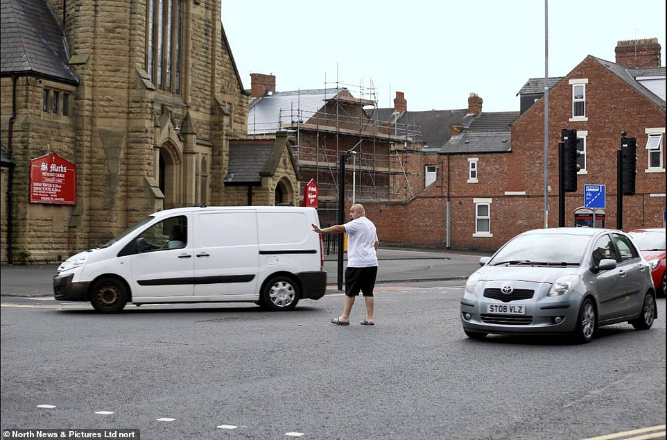 A motorist gets out of his vehicle to direct traffic after a power cut in the area leads to traffic lights failing in Gateshead