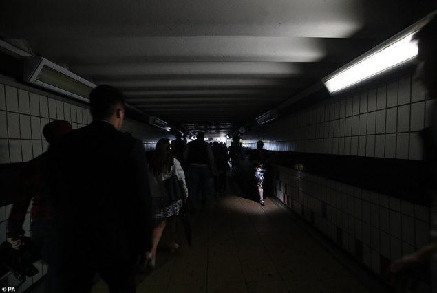 People walking in complete darkness at Clapham Junction station in London during a power cut