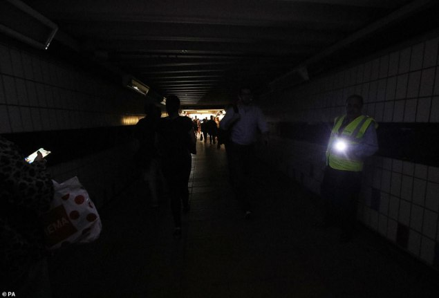 "People walking in complete darkness at Clapham Junction station in London during a power cut, which has caused ""apocalyptic"" rush-hour scenes across England and Wales"