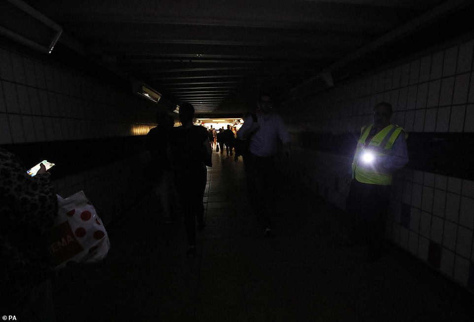 People walking in complete darkness at Clapham Junction station in London during a power cut, which has caused