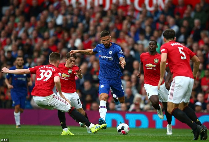 Chelsea forward Olivier Giroud tries to retain possession for his side as several United players close him down