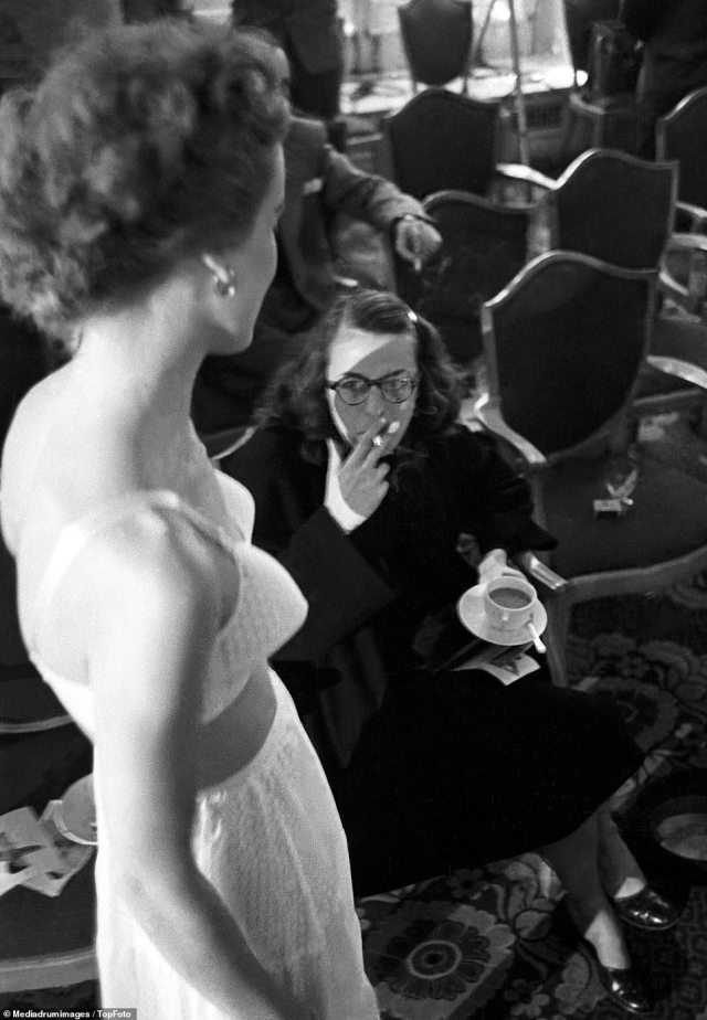 Skeptical: A woman smoking a cigarette, right, inspects the innovative bra on a model as she walks the catwalk