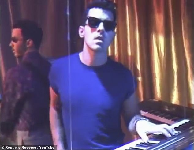 Tickling the ivories: Joe taps on a keyboard while Kevin holds down the guitar and Nick simply shows off his dance moves