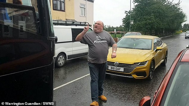 Pictured: The foul-mouthed man next to his 'BI8 OAF' car, which he screamed cost £40,000