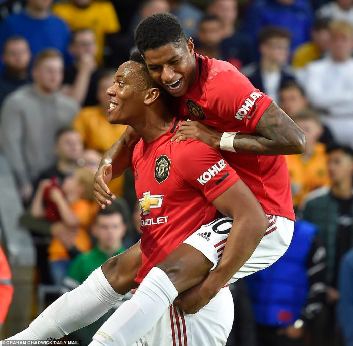 Marcus Rashford, who provided the assist, jumps on the goalscorer following his emphatic opener in the first half