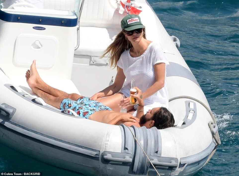 Golden couple: The pair sat close by one another as they headed out in a dinghy to catch some more rays
