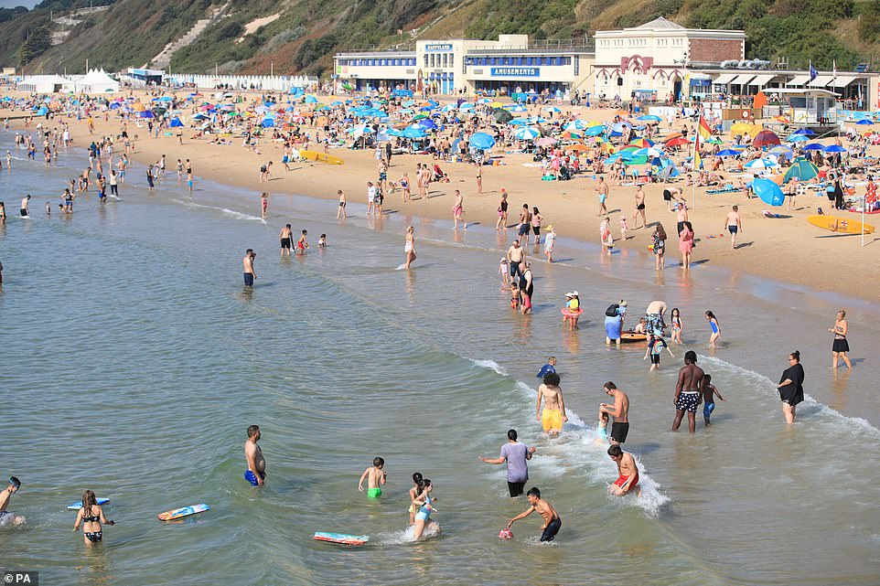 People on Bournemouth Beach enjoy the sunshine which is set to continue throughout the long weekend, with even hotter temperatures expected, possibly reaching a record high of 91F, most likely in the south-east of England, on Monday