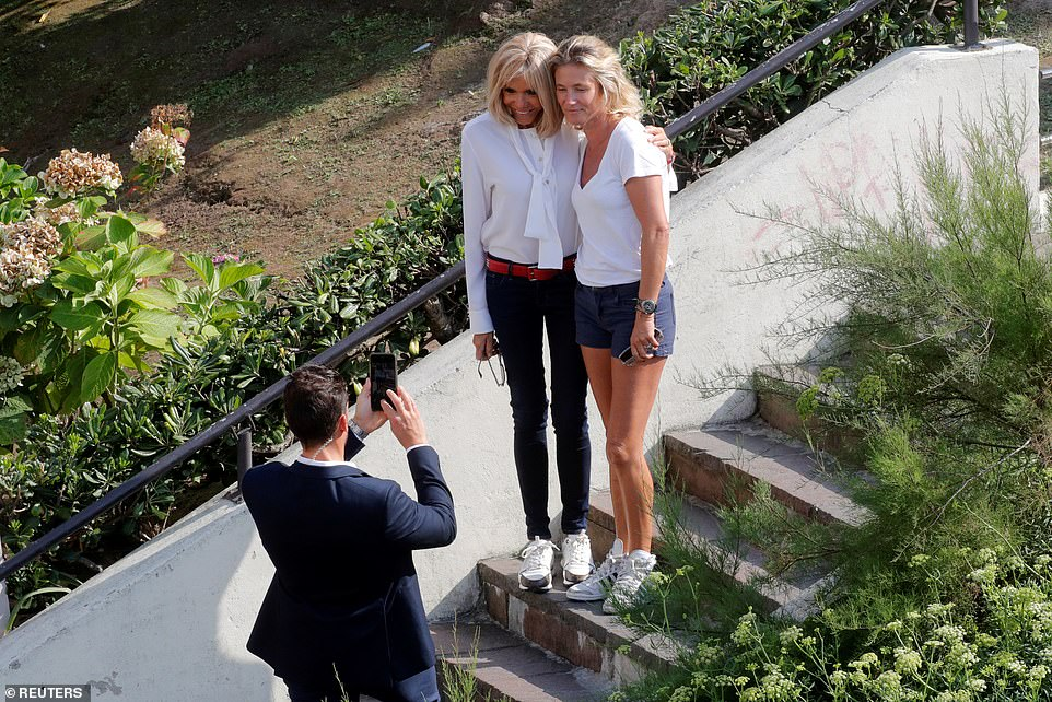 Brigitte Macron poses for a picture with an unknown woman near the summit venue during the G7 meeting in Biarritz