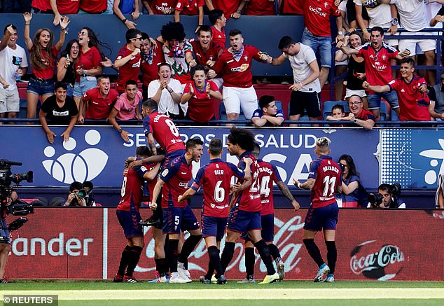 Torres is mobbed by his Osasuna team-mates after taking a shock lead at theEl Sadar Stadium