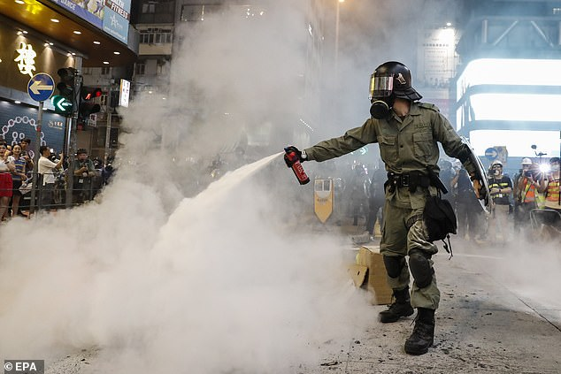 Ongoing protests in Hong Kong have also prompted affluent families in the city to consider an alternative citizenship. Pictured, a police officer tries to control the situation in a rally
