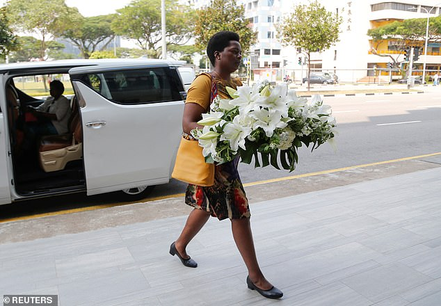 A visitor arrives with a wreath at funeral parlour Singapore Casket, where the body of late former Zimbabwe's President Robert Mugabe is being held