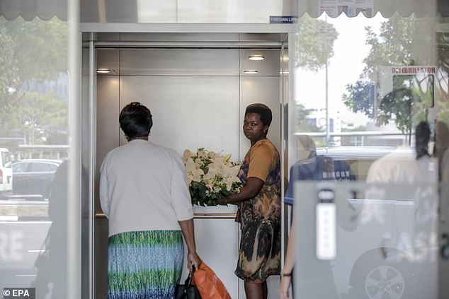 Visitors carrying wreaths enter the building as they prepare for a state funeral for the former leader