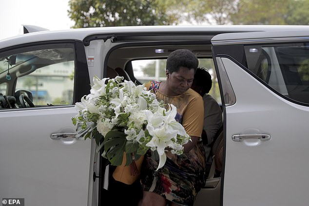 A friend arrives at the funeral parlour in Singapore holding a bouquet of lilies. Preparations have begun to give Robert Mugabe a state funeral