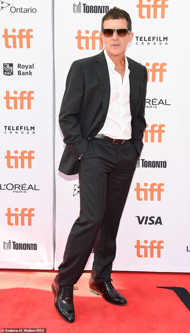 Relaxed: Spanish actor Banderas, 59, walked the red carpet in a black two-piece suit with his jacket undone over a white shirt and a large pair of sunglasses