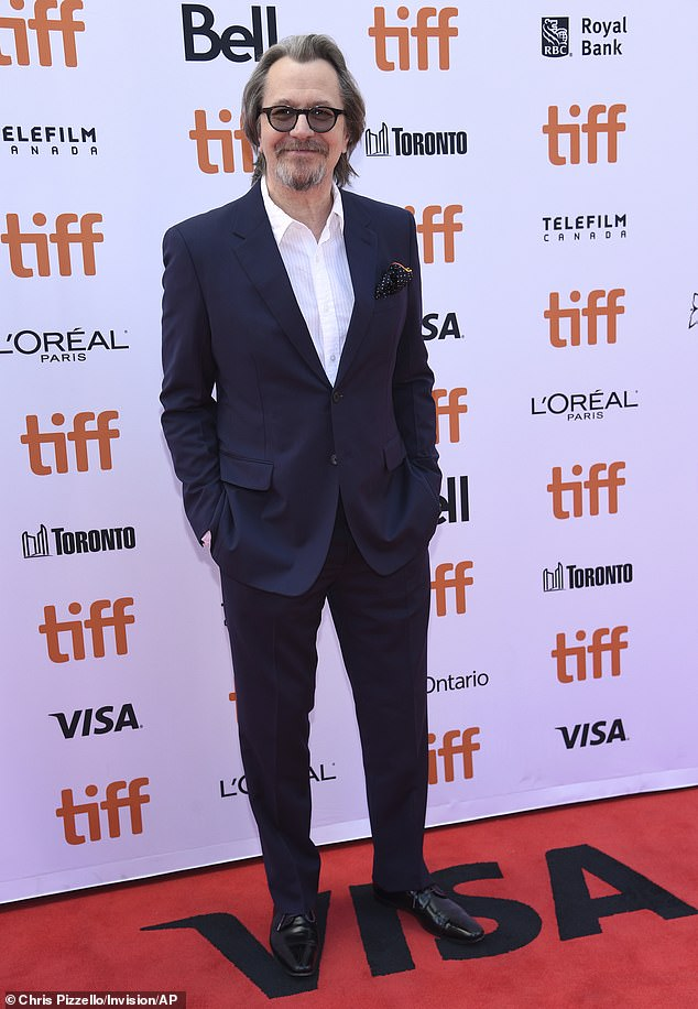 Looking good: Oldman, 61, put on a dapper show in a dark blue two-piece suit paired with a white dress shirt left unbuttoned at the collar and shiny black shoes