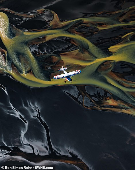 A small aircraft flies over the mesmerising landscape of Iceland