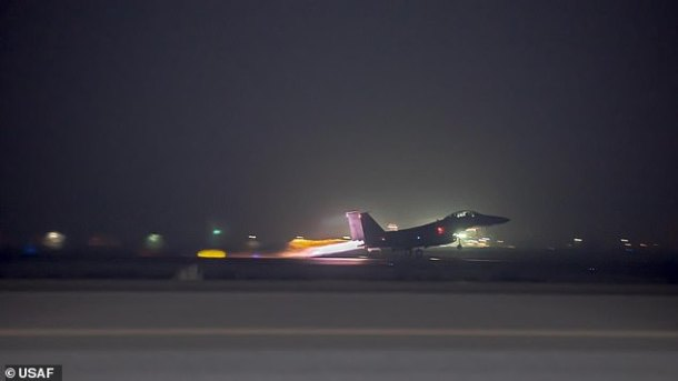 What appears to be the silhouette of an F-15 fighter is seen taking off from an airbase ahead of bombing runs on Qanus Island