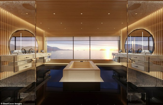 The master bathroom also features floor-to-ceiling windows looking out over the ocean, a large central bathtub, his-and-hers vanity units off to either side, and his-and-hers shower units to the left and right